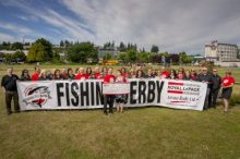 Entouré des organisateurs et des supporteurs, Stephen Grant, président de Royal LePage Advance, présente les fonds recueillis au Salmon Derby de Royal LePage Advance à Carrie Sjostrom de Campbell River et au North Island Transition Society. Photo : Eiko Jones Photographe.